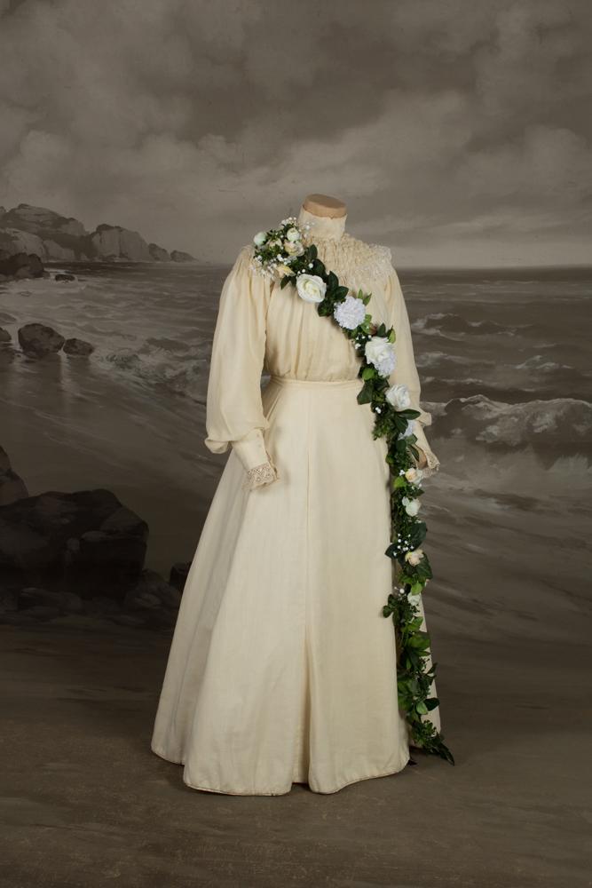 Mallinuken päällä vaalea hääpuku, jota koristaa runsas kukkaköynnös puvun miehustassa. Vuodelta 1906.