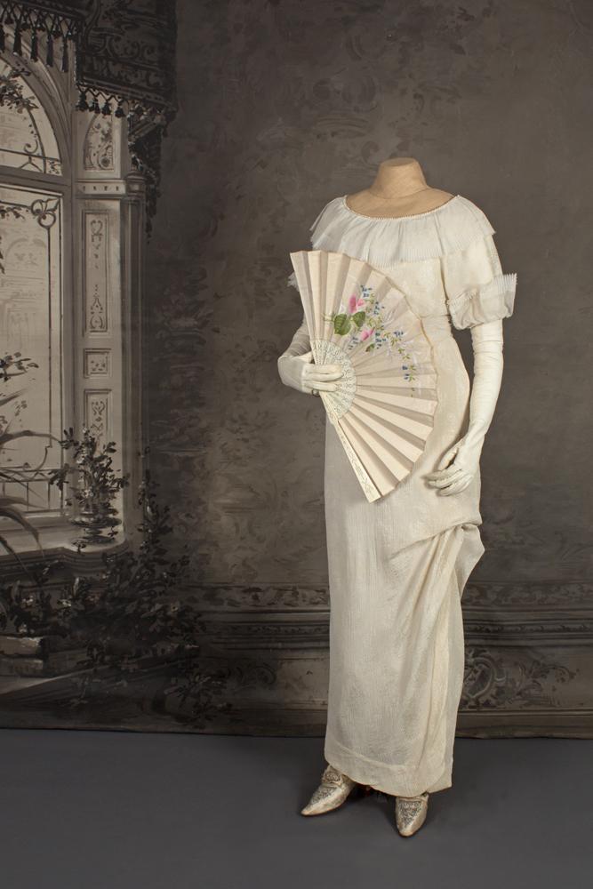 Mallinuken päällä vaaleaa silkkiä oleva kapealinjainen hääpuku vuodelta 1913. Kädessä viuhka.