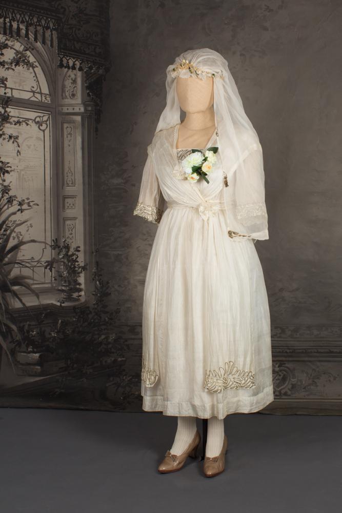 Mallinuken päällä vaaleaa silkkiä oleva hääpuku, joka ulottuu puoleen sääreen. Puku vuodelta 1920.,