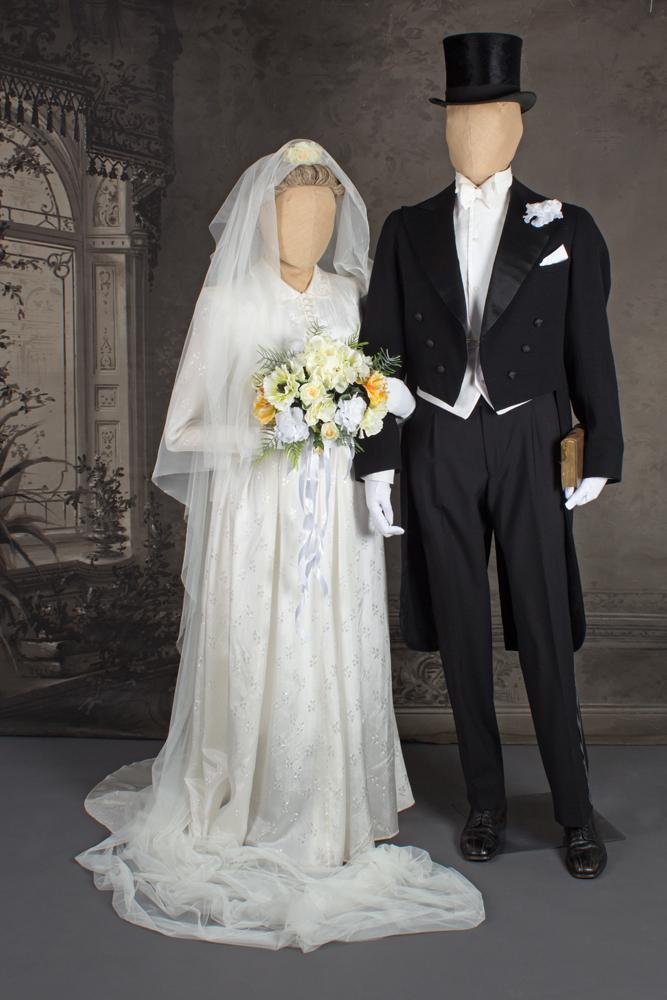 Mallinukkien päällä morsiamella valkoinen hääpuku ja sulhasella frakki. Vuodelta 1939.
