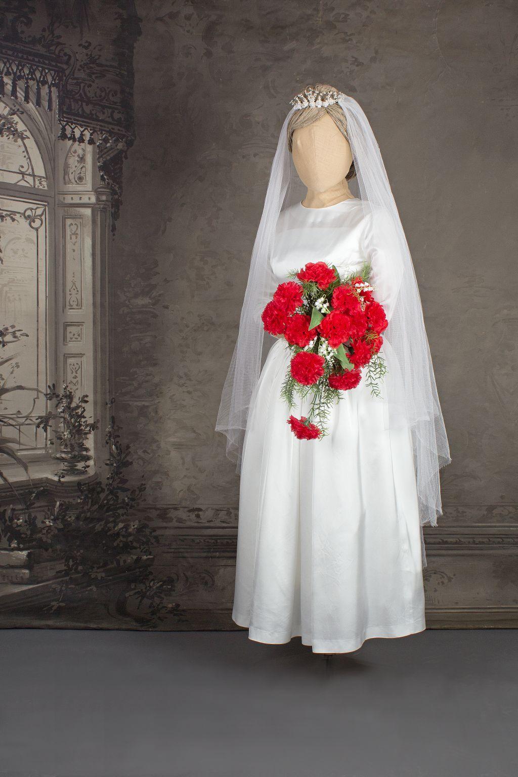 Mallinuken päällä valkea hääpuku. Kädessä kimppu punaisista neilikoista. Häät 1962