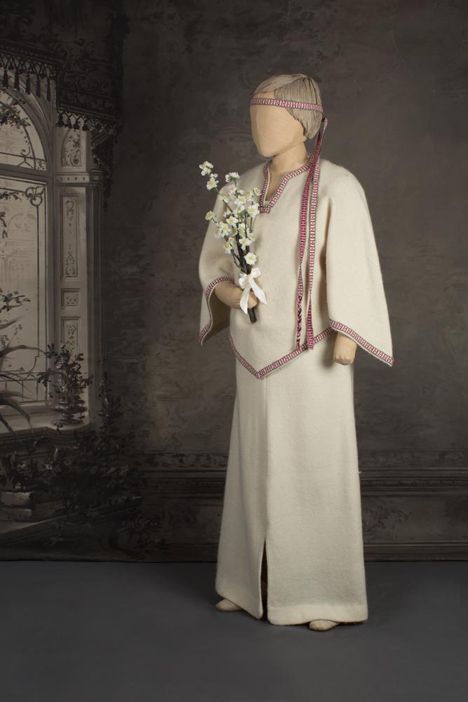Mallinuken päällä morsiamella vaaleasta villakankaasta tehty kansanomainen hääpuku. Päässä pirtanauha ja kädessä omenapuunoksa. Häät 1979.