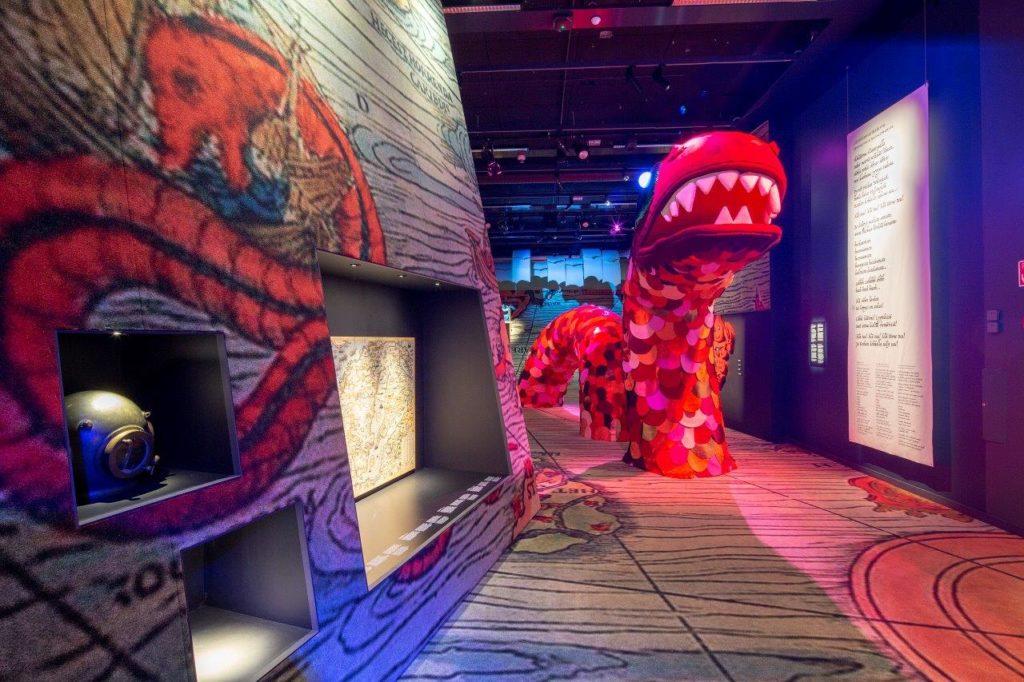Merimonsterit-näyttelystä yleiskuva. Sekä seinällä että lavastettuna, isona eläinhahmona näkyy punainen jättiläismerikäärme.