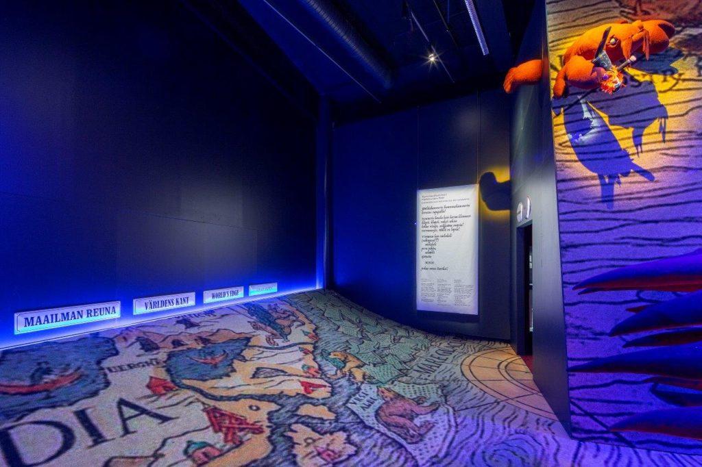 Merimonsterit-näyttely. Nouseva karttaa esittävä lattia ja seinä, jossa lukee maailman reuna.
