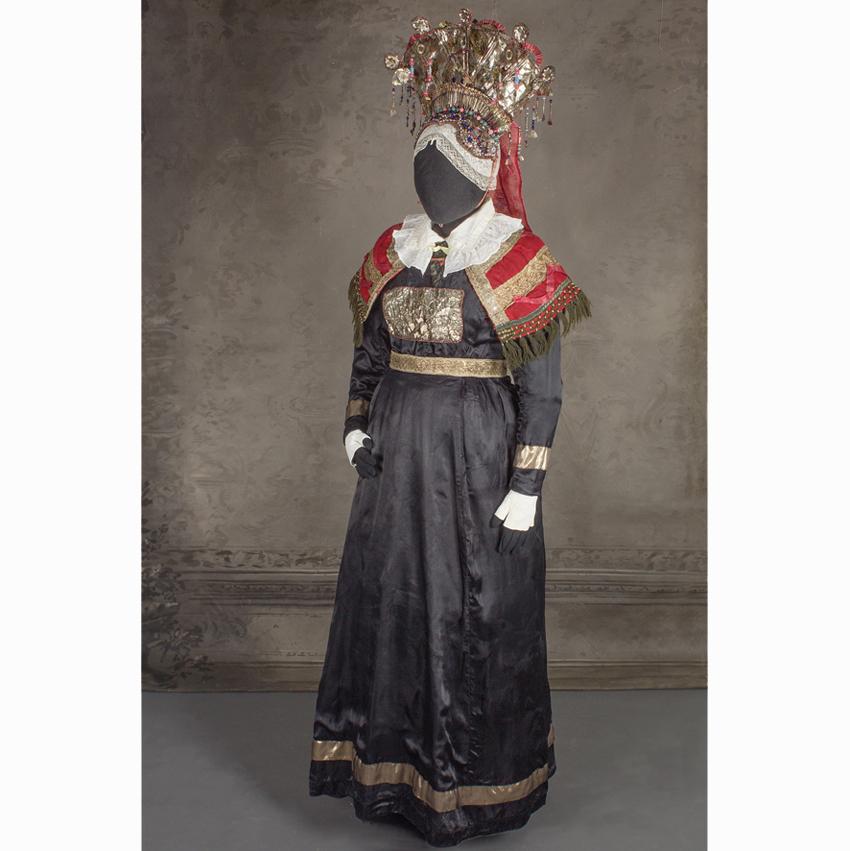 800-luvun kruunumorsiamen asu puettuna mallinuken päälle. Päässä korea helykruunu. Puku on musta.